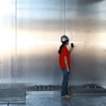 Supervisor inspecting magnetic shield installation of welded aluminum plate in an electrical distribution room.