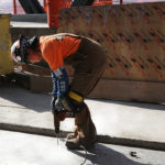 Ironworker installing magnetic shielding materials on floor.